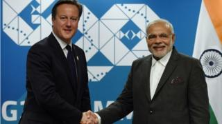 """In this file photo taken on November 14, 2014, Britain""""s Prime minister David Cameron (L) shakes hands with India""""s Prime Minister Narendra Modi (R) during a bilateral meeting on the sidelines of the G20 Summit at the Brisbane Convention and Exhibitions Centre (BCEC) in Brisbane."""