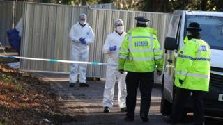 Uniformed police and forensic investigators at scene of car fire