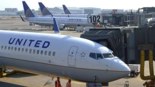 Two ground crew members walk past a United Airlines airplane as it sits at a gate at Newark Liberty International Airport