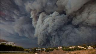 A massive smoke plume, powered by strong winds, rises above the the Woolsey Fire