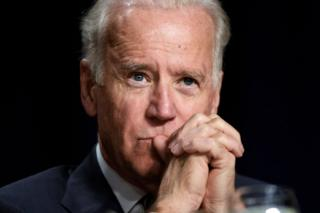 Joe Biden with his hands clasped in front of him