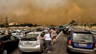 Cars are blocked at the closed National Road during a wildfire in Kineta, near Athens
