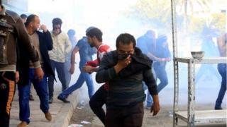 أحد المتظاهرين يغطي وجهه بعد اطلاق قوات الأمن الغاز المسيل للدموع