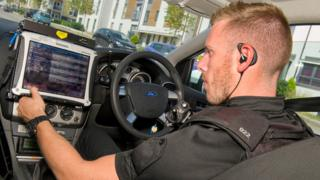 Police officer using a computer in a patrol car in Bristol