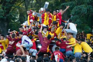 Filipino Roman Catholic devotees climb the carriage to kiss and rub with their towels the image of the Black Nazarene. Manila, Philippines, Monday 9 January 2017.