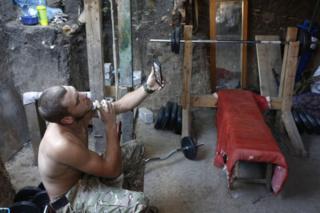 Украинский военный бреется, глядя на свое отражение в мобильном телефоне. Линия фронта вблизи Маруиполя, 12 июня 2018 года