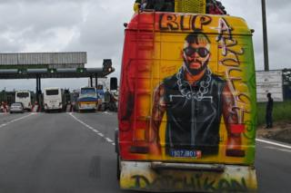 A mini bus with graffiti depicting the late Ivorian DJ Ange Didier Houon aka DJ Arafat on the highway near Abidjan