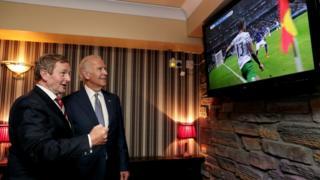 """Joe Biden (right) and Taoiseach Enda Kenny watching the Ireland v Italy match in Coady""""s Pub, Castlebar,"""