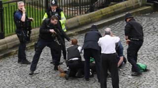 Police hold a gun to a man on the ground during Westminster attack