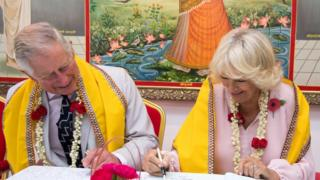 Charles and Camilla sign the visitors' book at a Hindu temple in Bahrain