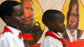 """Two children are pictured in front of the portraits of the former Cuban president Fidel Castro and the former South Sudanese leader John Garang at the memorial service for the former Cuban president Fidel Castro organised by the Red Army and the Sudan People""""s Liberation Movement (SPLM) in the SPLM House in Juba, South Sudan, on December 4, 2016."""