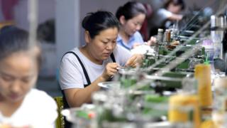 Women work at sewing machines in a factory in China in 2018