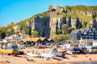 A beach with a cliff railway in the background