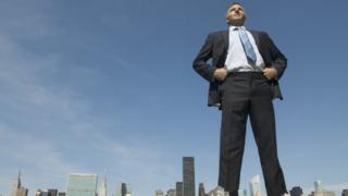 Tall man towering over city landscape