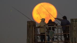 Un grupo de pescadores bajo la luna en Redondo Beach, California.