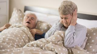 Older woman covering her ears in bed