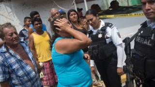Relatives of five people murdered on a street cry in Acapulco's Icacos neighbourhood