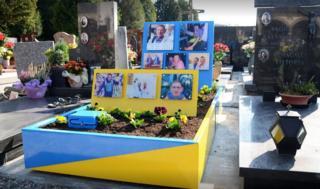 La tumba de Carlo Annoni, una estructura azul y amarilla con coloridas fotos suyas
