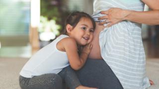Criança ouve a barriga da mãe