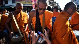 People give alms to Buddhist monks during a mass prayer one week after a lone soldier shot and killed 29 people in Thailand
