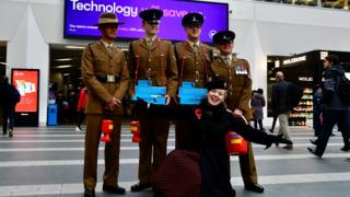 Singer Fiona Harrison with soldiers at New Street Station