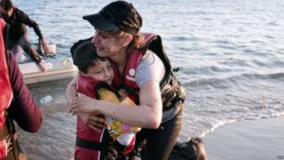 A migrant woman hugs her son after safely arriving to the shores of the Greek island of Kos on 18 August 2015