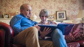 Ray and Alison Johnson at home in Wisbech. Elliott's graduation photograph sits behind them on the mantelpiece
