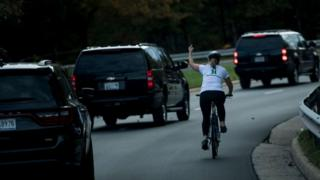 Ms Briskman cycling past the motorcade, making an obscene gesture.