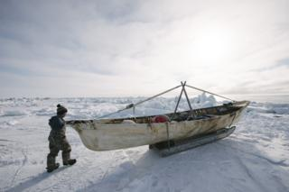 Six-year old Steven Reich examines his father's umiaq, or skin boat used for whaling.