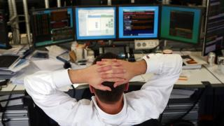 Currency trader leans back and looks at screens