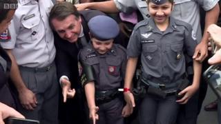 Žair Bolnosaro savija prste u obliku pištolja sa decom obučenom u policijske uniforme