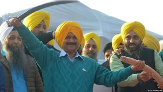 Arvind Kejriwal (C) holds a sword presented by AAP leader Jaswinder Singh and AAP MP Bhagwant Mann during an AAP rally in Majitha, some 25 kms from Amritsar on December 14, 2016