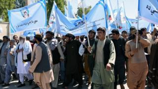دغه کسان، چې د سولې په شعارونو سمبالې جنډې له ځان سره لېږدوي، د جګړې او افغان وژنې ضد شعارونه ورکوي.