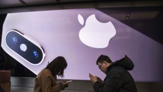 שני אנשים מסתכלים על מכשירי האייפון שלהם בחנות של אפל, המתגמדים מתמונת קידום מכירות אדירה לדגם האחרון