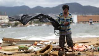 Una mujer entre escombros tras el paso de la tormenta Carlos