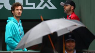 Andy Murray looks out on to rainy tennis court