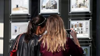 Two women study houses for sale