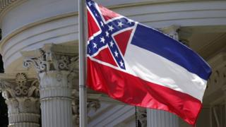 The state flag of Mississippi is unfurled against the front of the Governor's Mansion in Jackson, Miss., Tuesday, June 23, 2015
