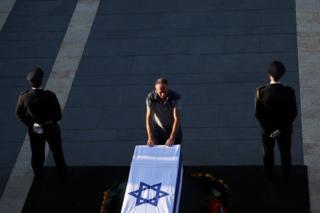 تابوت شیمون پرز در بیرون ساختمان پارلمان اسرائیل در بیتالمقدس قرار گرفته و در این عکس یک مرد در حالی که دو سرباز گارد تشریفات کنار تابوت ایستاده اند به آن احترام میگذارد