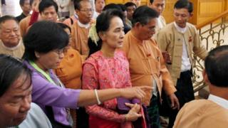 """Myanmar's pro-democracy leader Aung San Suu Kyi, center, arrives to participate in the inaugural session of Myanmar""""s lower house parliament Monday, Feb. 1, 2016 in Naypyitaw, Myanmar."""