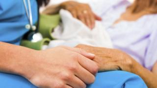 Nurse holding patients hand
