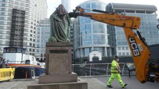 Workmen taking down Robert Milligan statue