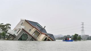 in_pictures This photo taken on 15 July 2020 shows residents riding a boat past a damaged and flood-affected house near the Poyang Lake due to torrential rains in Poyang county, Shangrao city in China's central Jiangxi province