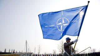 A solider with a Nato flag at a ceremony in Germany