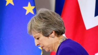 The British and EU flags behind Theresa May, who is looking down