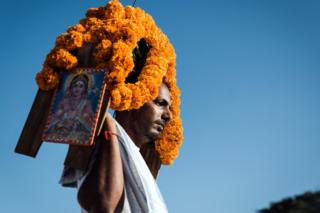 "A Hindu worshipper carries a ""kavadi"" or offering on his shoulders"