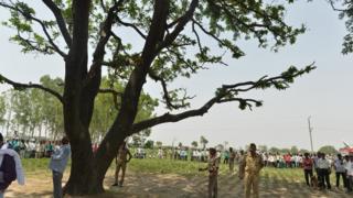 Villagers and police collect near tree where the girls were found in Badaun