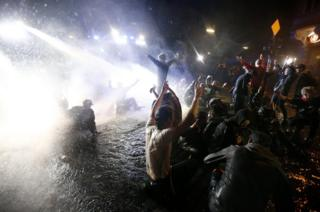 Protesters show V-signs and shout slogans as German police use water cannon during the demonstration at the G20 summit in Hamburg, Germany
