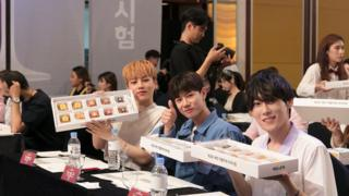 Three South Korean young men give thumbs up and show boxes with ten pieces of fried chicken for blind tasting