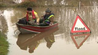 Two people in a boat on a flooded road